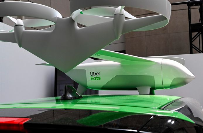 De drone bovenop een Uber-wagen.