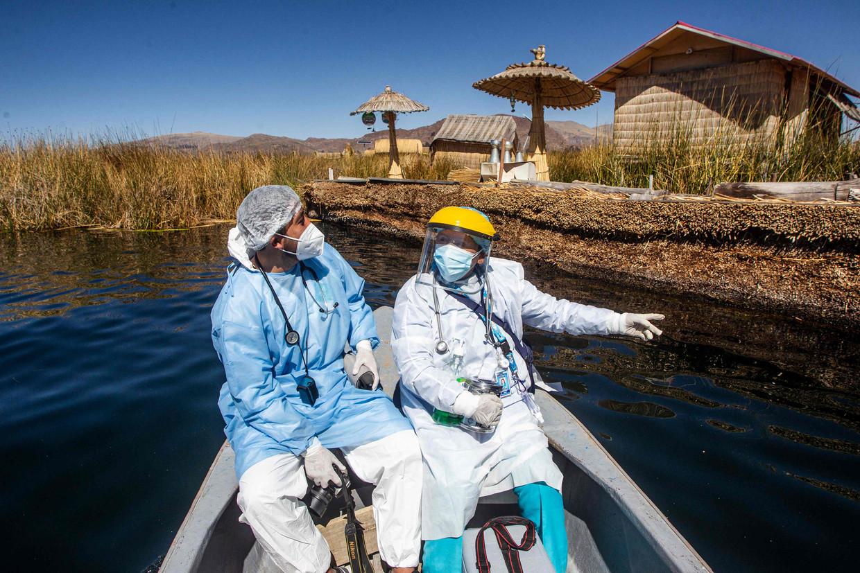 Een vaccinatieteam is onderweg naar de Uros-eilanden in het Titicacameer in Peru om de bewoners in te enten tegen corona.  Beeld Carlos Mamani / AFP