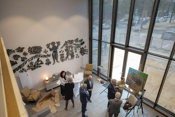 De nieuwbouw van Neos aan de Boutenslaan werd vrijdag geopend in het bijzijn van wethouder Renate Richters (l). Aan de wand van de gemeenschappelijke huiskamer hangt een stenen reliëf uit het oude Labrehuis.