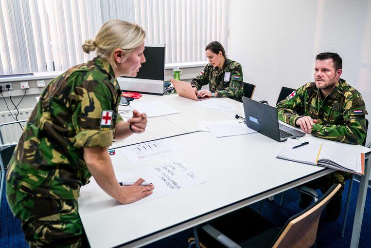 Militaire planners van Defensie en de Brabantse ziekenhuizen overleggen over de verplaatsing van coronapatiënten naar andere ziekenhuizen. Deze militairen zijn binnen de krijgsmacht getraind in het plannen van patientenvervoer.  Beeld ANP