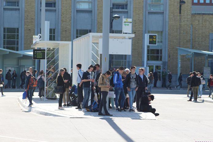 Jongeren wachten vergeefs op een bus aan het station.