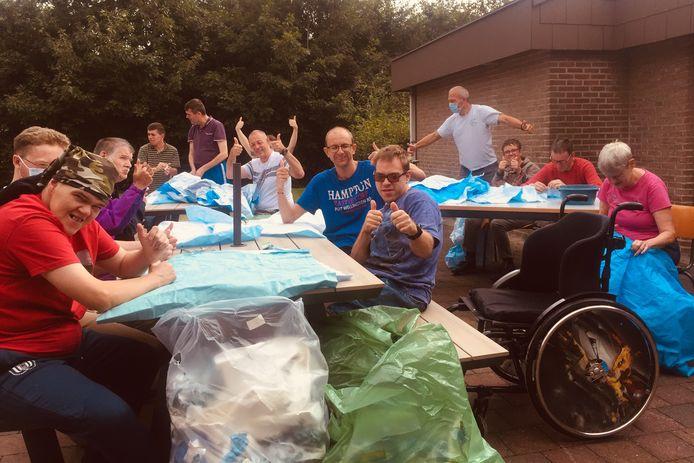 De bewoners van 'Ons Tehuis Brabant' sorteren de doeken voor recyclage..