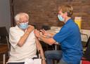 Pieter Seghers krijgt de vaccinatie van een medewerker GGD Zeeland in het dorpshuis in Rilland.
