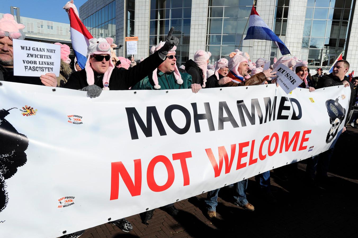 Demonstranten van de anti-islambeweging Pegida protesteren in september vorig jaar met een varkensmasker voor het stadhuis in Amsterdam tegen het vluchtelingenbeleid