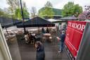 Het makelaarsbord 'te koop' van de buren van Café Vrijdag pal voor het uitgebreide terras.