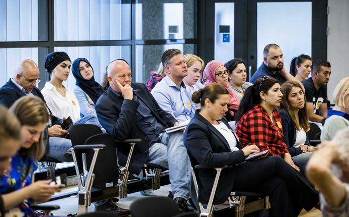 Gedupeerde klanten van het Eindhovense gastouderbureau Dadim volgen in de Tweede Kamer het debat over de stopzetting van hun kindertoeslag