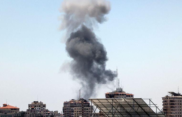 Rookwolken van een Israëlische luchtaanval in Gaza-stad, op 19 mei 2021. - Oorverdovende luchtaanvallen en raketbeschietingen op Gaza. De internationale diplomatieke druk om een staakt-het-vuren tot stand te brengen na meer dan een week van bloedvergieten neemt toe.  Beeld AFP