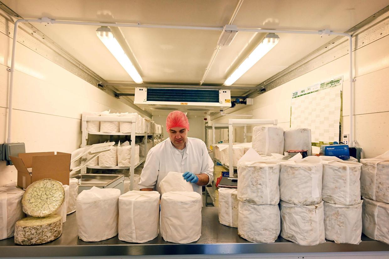 Een handelaar is in de weer met zijn blokken typisch Britse stilton-kaas. Sinds de brexit is het exporteren ervan naar de EU door extra formaliteiten bijzonder duur geworden. Beeld AFP