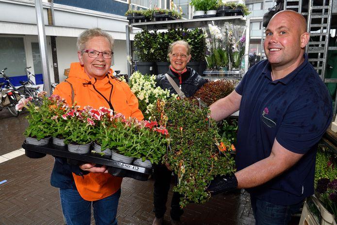 Bloemist Cees van der Plas geeft Rita Cazemier gratis plantjes, op de achtergrond staat dochter Saskia.