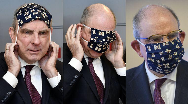 Minister Koen Geens terwijl hij het mondmasker probeert aan te doen.