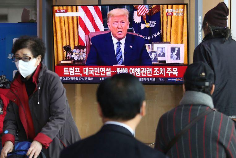 Pendelaars in de Zuid-Koreaanse hoofdstad Seoel kijken naar de toespraak  van Donald Trump. Beeld AP