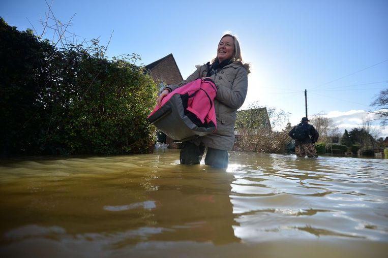Clare Mallard waadt met een tas door het water in het dorpje Wraysbury, Berkshire.<br /><br />De Engelse overheid waarschuwt voor ernstig overstromingsgevaar in 14 plaatsen langs de de rivier de Theems. Duizenden huishoudens moeten zich daar op voorbereiden. Sinds december zijn al zo'n 8000 woningen getroffen door het hoge water.<br /><br />Ondanks alle maatregelen is vanmiddag het dorp Datchet ook ondergelopen.<br /><br />Na twee maanden van recordneerslag voorspellen meteorologen nog zeker tot en met donderdag iedere dag regen. Vooral de graafschappen Berkshire en Surrey zullen vermoedelijk met wateroverlast te maken krijgen. <br /><br />De Britten worstelen met het natste weer sinds 1766. Het water in de rivier stond in tientallen jaren niet zo hoog en stijgt nog steeds. Beeld afp