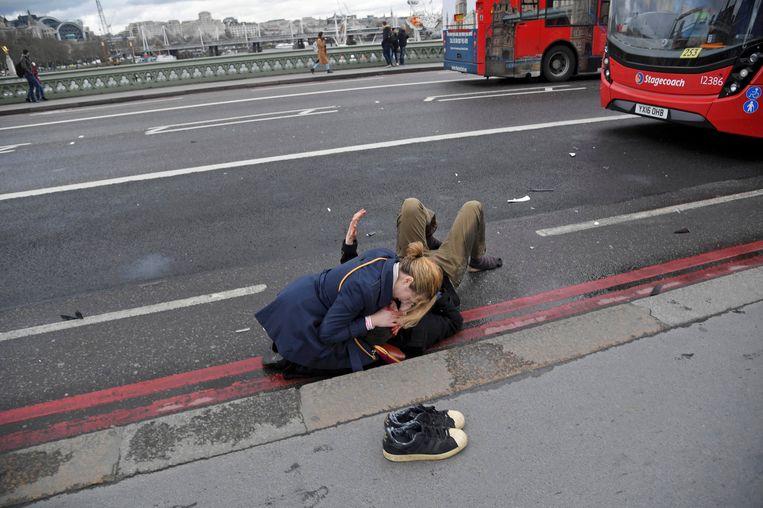 Een vrouw helpt een gewonde man op de Westminster Bridge. Beeld REUTERS