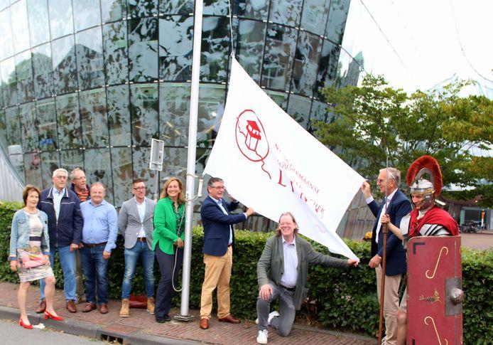 Jack en Monique Veldman van Archeon hijsen de Limes vlag bij het stadhuis van Alphen, samen met wethouder Kees van Velzen en archeoloog Tom Hazenberg (zittend)