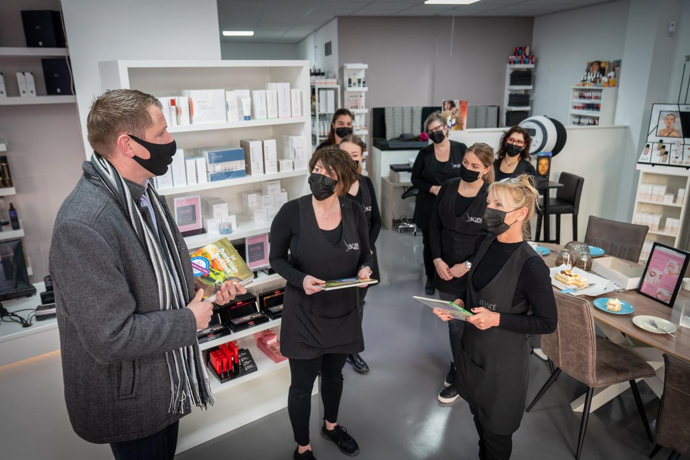 Wethouder Horsthuis-Tangelder kwam Carola Janssen (links) en Carin Teunissen (rechts) en hun personeel feliciteren met de heropening. Als cadeautje nam hij het Overbetuws Kookboek mee. ,,Ik ben blij dat er weer verruiming mogelijk is, maar we moeten ook voorzichtig blijven met dit virus.''