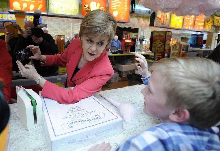 Sturgeon praat met een kind tijdens de campagne voor de aankomende Britse parlementsverkiezingen. Beeld afp