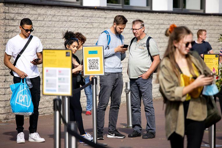 Bezoekers bij het Van Gogh Museum in Amsterdam met hun mobiele telefoon. Het kabinet overweegt de invoering van een coronapas voor horeca en culturele instellingen.  Beeld Hollandse Hoogte / ANP