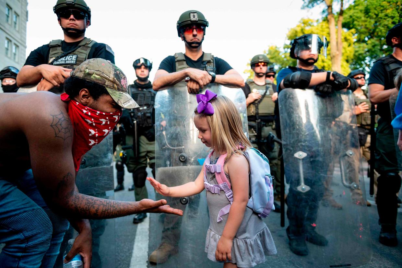 Begroeting tussen Mikaela (3) en George (29) bij protesten na de dood van George Floyd, vlak bij het Witte Huis. Beeld Roberto Schmidt / AFP