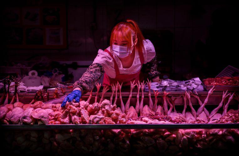 Een Chinese vleesverkoopster in haar stalletje op een voedselmarkt in Peking.  Beeld Getty Images