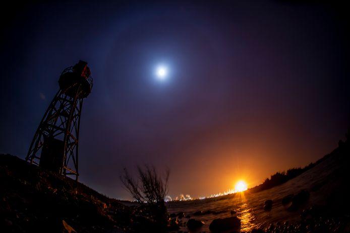 Beeld vanuit Strijensas van het affakkelen bij Shell aan de overkant van het Hollandsch Diep in oktober 2020. (Naast de oranje gloed van Shell  was er ook nog een volle maan met halo.)