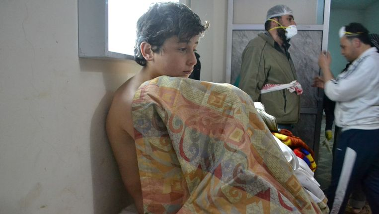 Een jongen zit op een bed op in een kliniek in het Syrische dorp Sarmin in verband met de gasaanval in het gebied. Beeld anp