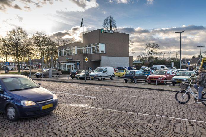 Het Burgemeester Hasselmanplein - met de ABN Amro en het parkeerterrein - op archiefbeeld in 2015.