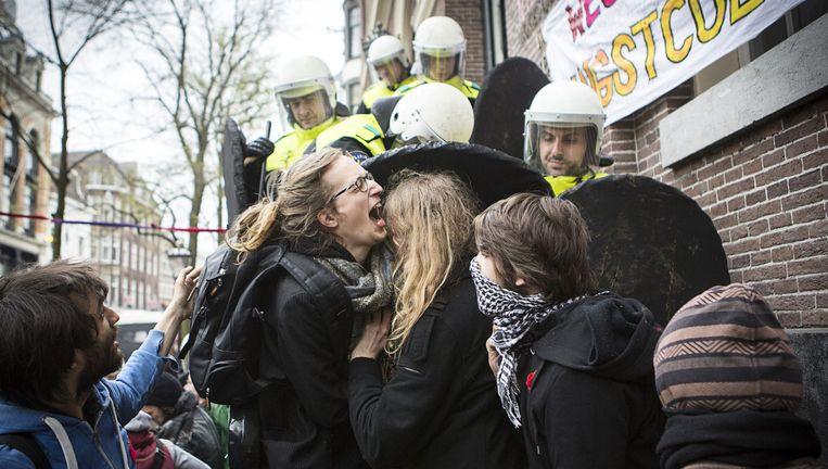 ME'ers duwen zaterdag studenten het bordes van het Maagdenhuis aan het Spui in Amsterdam af. Beeld anp