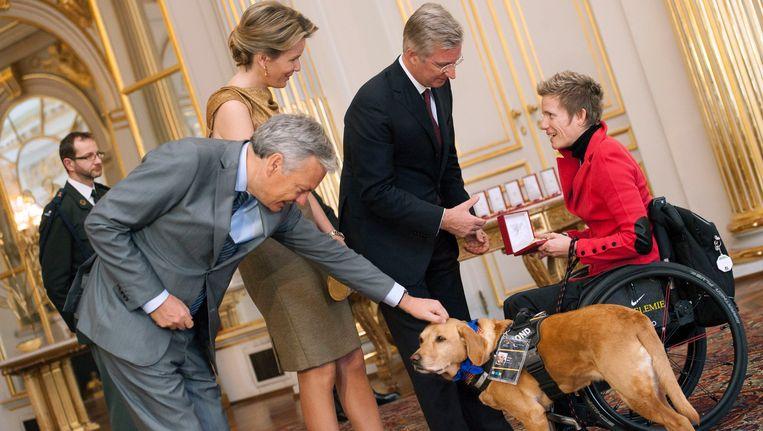 Marieke Vervoort met haar hond Zenn tijdens een ontvangst op het koninklijk paleis met Didier Reynders, koningin Mathilde en koning Filip. Beeld PHOTO_NEWS