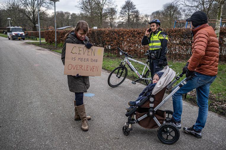 Patricia Waijers en Ivo van den Heuvel met hun kind en een agente. Beeld Joris van Gennip