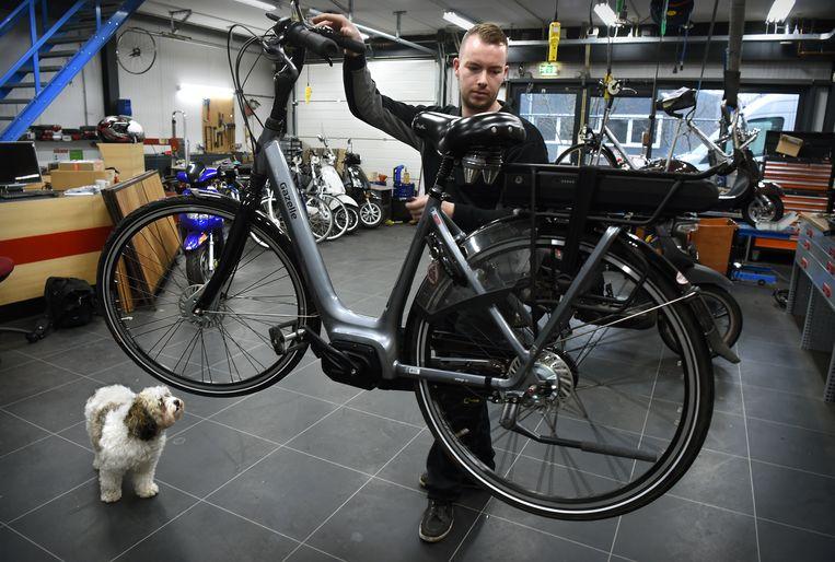 Een fietsenmaker aan het werk in Druten.  Beeld Marcel van den Bergh