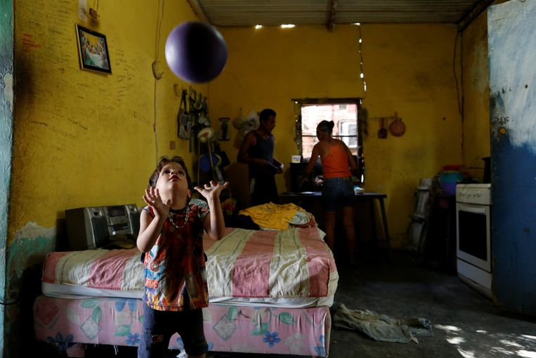Child plays with a ball next to his parents. Beeld REUTERS