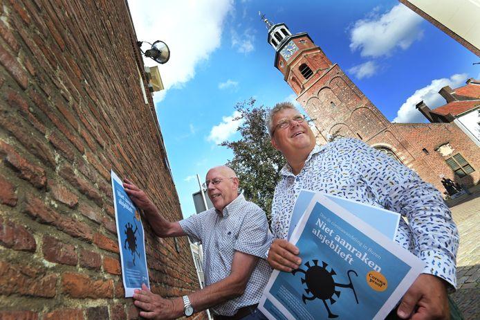 Fred Eggink (links) en Mark Hofman testen het ophangen van posters en coronagedichten in de binnenstad van Buren