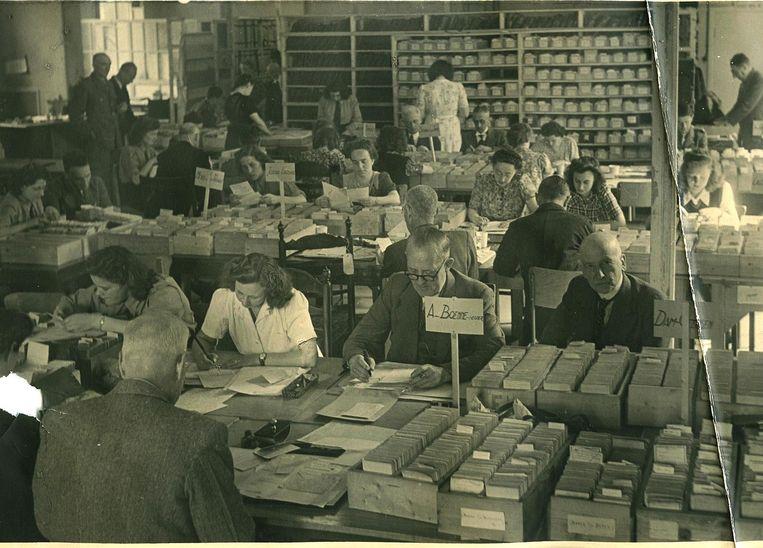 Medewerkers van het Nederlandse Rode Kruis zoeken vlak na de oorlog naar de sporen van vermiste Joodse gedeporteerden. Beeld Nederlandse Rode Kruis, oorlogsarchief