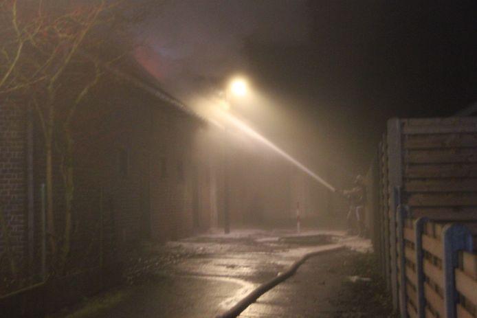Een brandweerman aan de slag aan de achterkant van het jeugdhuis in Izegem.