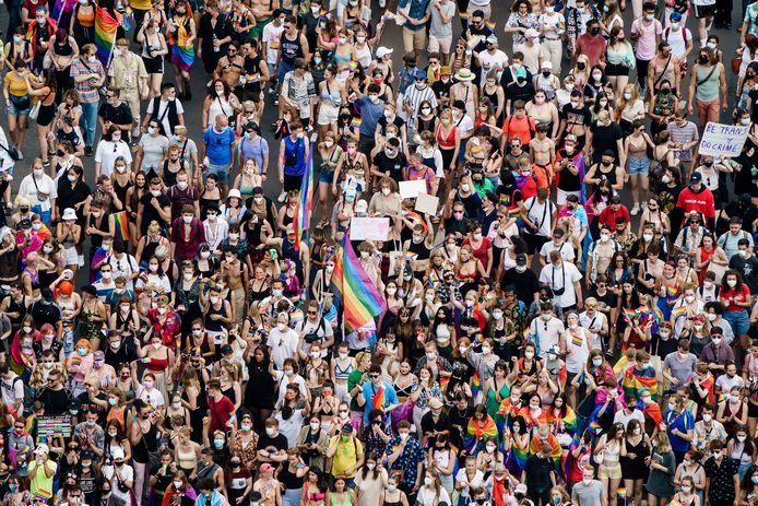 """Un participant dans la foule tient un carton sur lequel on peut lire """"CSD au lieu de AfD"""" en guise de déclaration contre le parti de droite Alternative pour l'Allemagne (Alternative für Deutschland), sur la Leipziger Strasse, pendant le défilé du Christopher Street Day """"CSD Berlin 2021"""" à Berlin, en Allemagne, le 24 juillet 2021."""