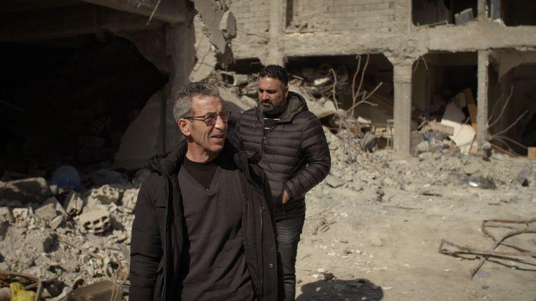 Houssein op zoek naar dochter en kleinkinderen, met op de achtergrond programmamaker Sinan Can.  De foto's komen uit de documentaire De verloren kinderen van het kalifaat Beeld BNN/VARA