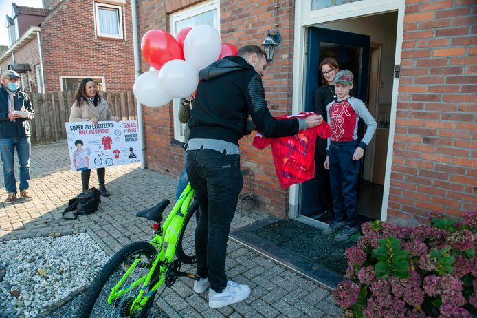 Mike Nieuwkoop uit Eethen heeft een ontwerpwedstrijd voor een sportshirt gewonnen en ontvangt uit handen van wielrenner Lars Boom het shirt en een nieuwe mountainbike.