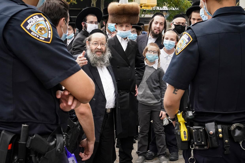 Leden van de joods-orthodoxe gemeenschap in de wijk Borough Park spreken met de politie. Beeld AP