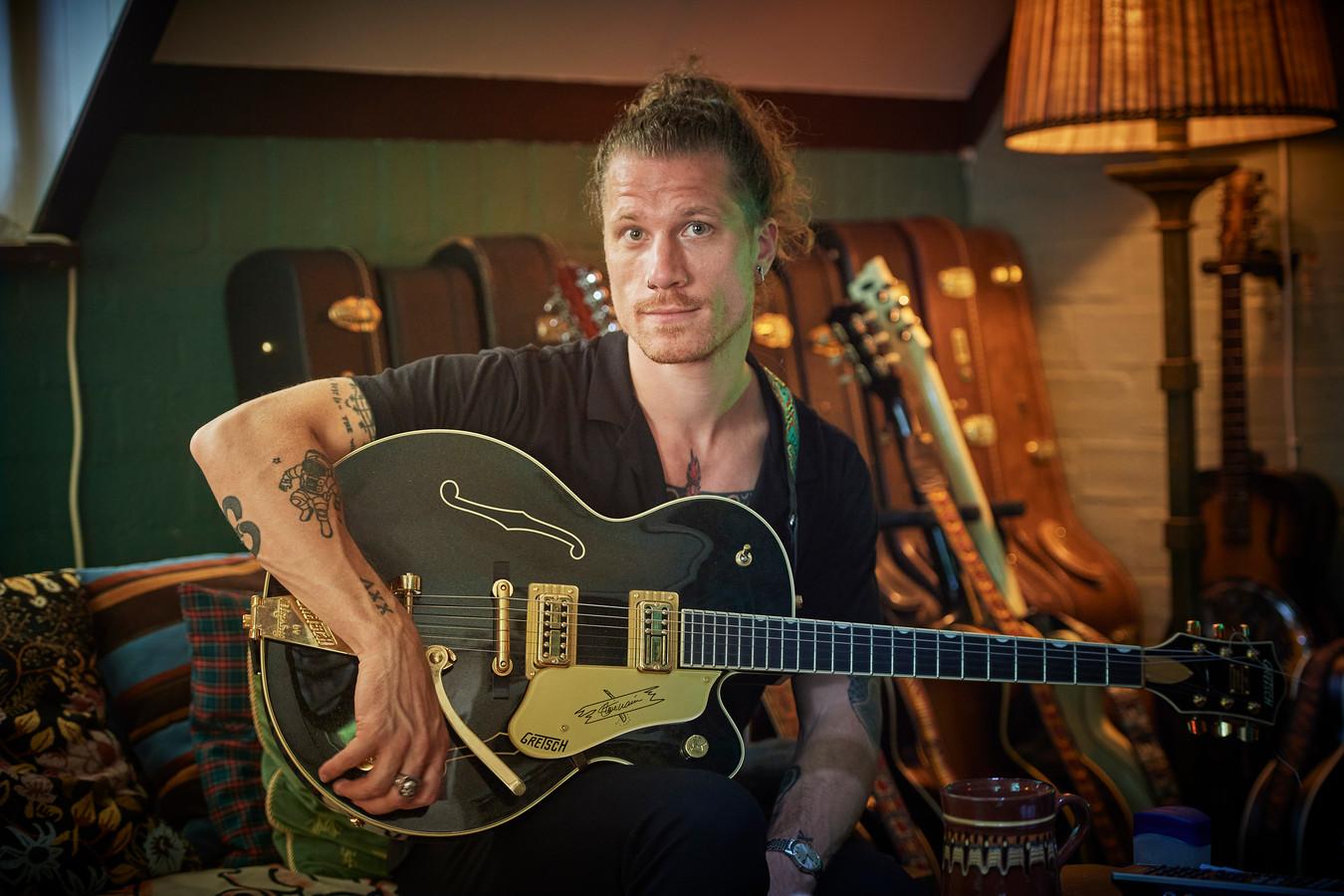 """Robin Borneman in zijn woonkamer tussen en met zijn gitaren. ,,Ik ben meer een zanger met een gitaar, dan een gitarist die ook zingt."""""""