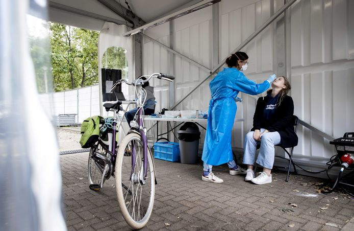 Een medewerker van de GGD neemt een coronatest af in een testlocatie. Wegens de stijging in het aantal besmettingen zijn veel testlocaties overbelast.