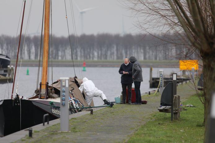 De forensische recherche onderzoekt het lichaam in de boot bij de havenmonding in Spakenburg.