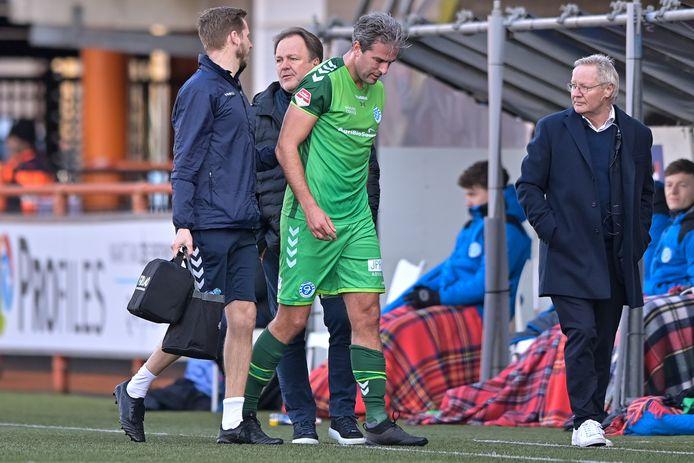 De Graafschap-aanvoerder Ralf Seuntjens verlaat met een enkelblessure het veld. Achter hem kijkt trainer Mike Snoei zuur toe.
