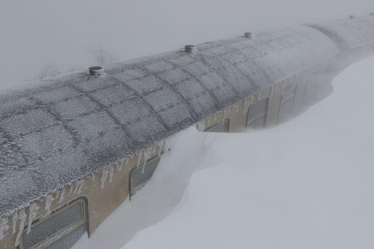 In Schierke in de Duitse deelstaat Saksen-Anhalt raakte zelfs een toeristentrein zo goed als volledig bedolven door de sneeuw. Beeld Matthias Bein/dpa-Zentralbild/dp