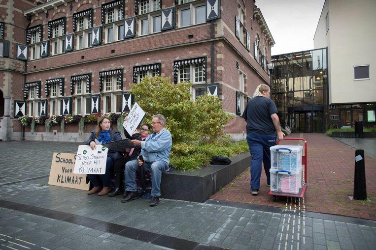 Lilly (11) staakt iedere week een uur voor het klimaat bij het gemeentehuis van Zeist. Dit keer doet haar moeder mee.  Beeld Werry Crone