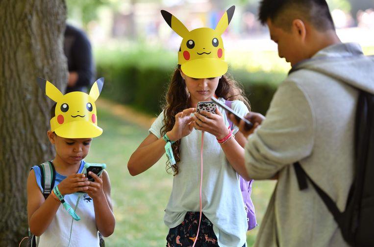 Kinderen met Pikachu-hoedjes spelen Pokemon Go in Dortmund.  Beeld AFP