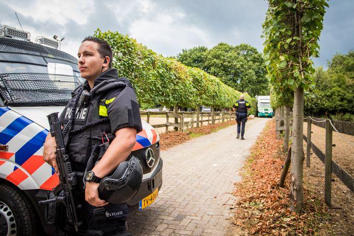 Zwaarbewapende agenten bewaken het drugslab in Overasselt dat afgelopen augustus werd ontmanteld.