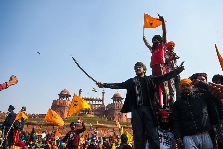 Demonstrerende boeren zwaaien met zwaarden en vlaggen voor het iconische Rode Fort in het hart van de oude stad van Delhi.  Beeld AFP