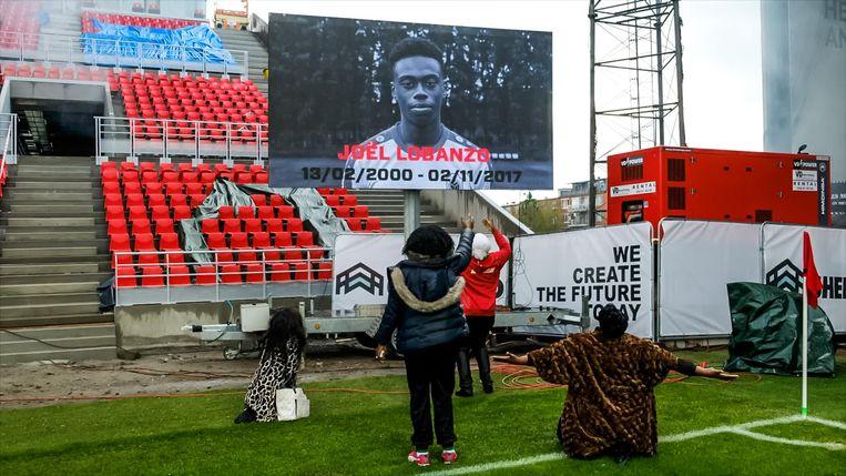 Zijn familie valt op de knieën voor het scherm met de beeltenis van de overleden Joël Lubanzo.