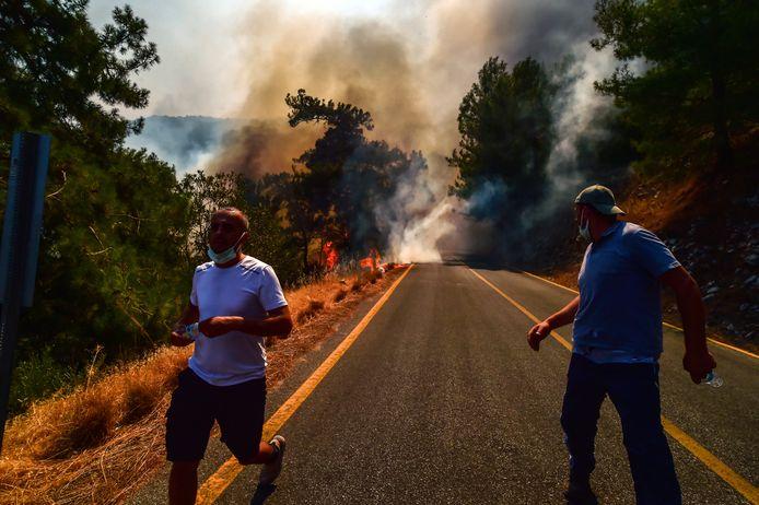 Des personnes s'enfuient alors que des feux de forêt ravagent une zone proche du bord de mer, obligeant les gens à être évacués par bateaux, à Bodrum, Mugla, Turquie, dimanche 1er août 2021.