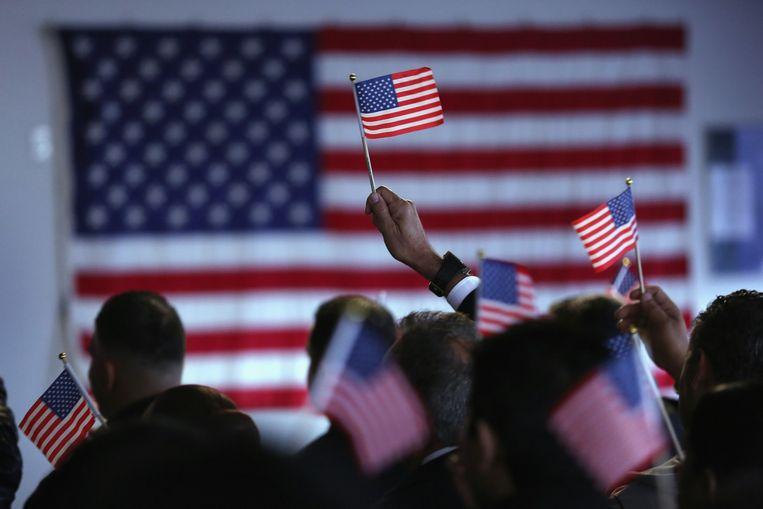 Vlaggetjes bij een neutralisatieceremonie waarbij immigranten Amerikaans staatsburgerschap krijgen Beeld getty